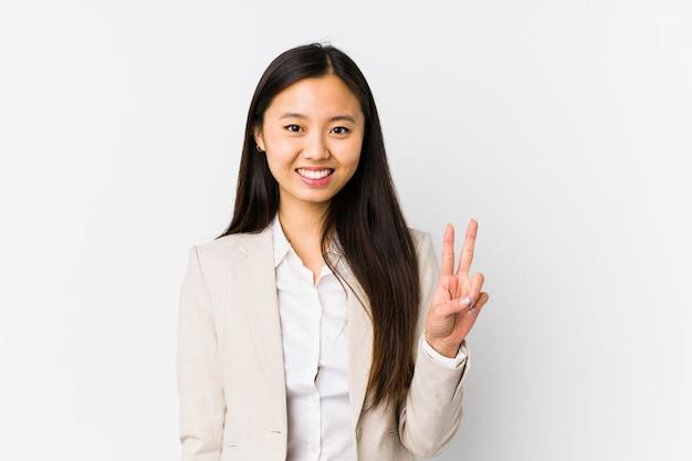 Jeune femme d'affaires chinoise isolée montrant le signe de la victoire et souriant largement.
