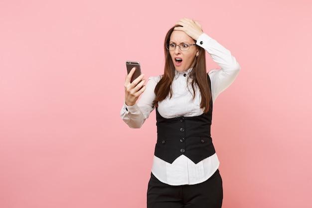 Jeune femme d'affaires choquée et irritée dans des verres regardant sur un téléphone portable et s'accrochant à la tête isolée sur fond rose. dame patronne. concept de richesse de carrière de réalisation. copiez l'espace pour la publicité.