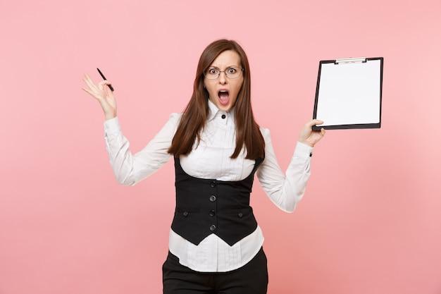 Jeune femme d'affaires choquée et irritée tenant une tablette de presse-papiers avec un espace de copie d'espace de travail de feuille vide vierge isolé sur fond rose pastel. dame patronne. réalisation carrière richesse. espace publicitaire.