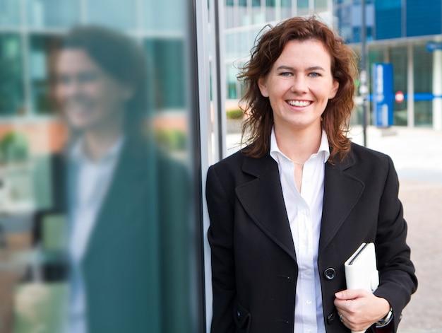 Jeune femme d'affaires confiant avec un organiseur personnel près de l'immeuble de bureaux