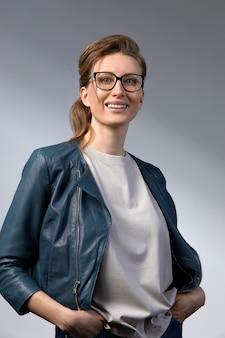 Jeune femme d'affaires confiante de 35 à 45 ans, blonde en vêtements et lunettes élégants, fond gris, gros plan. concept de réussite commerciale et professionnelle.