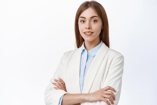Jeune femme d'affaires confiante en costume, les bras croisés sur la poitrine et le sourire devant, l'air déterminé et habile, debout sur un mur blanc