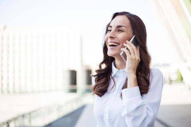 Jeune femme d'affaires confiante heureuse utilise son smartphone tout en marchant à l'extérieur dans une ville urbaine