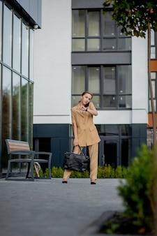 Une jeune femme d'affaires confiante de race blanche adulte parle au téléphone à l'extérieur près d'un immeuble de bureaux moderne.
