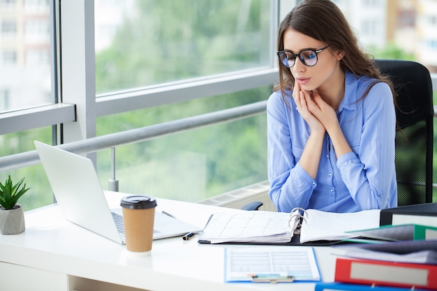 Jeune femme d'affaires confiante travaillant au bureau et en tapant avec un ordinateur portable.