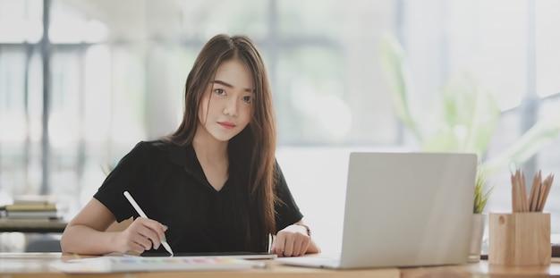 Jeune femme d'affaires confiante travaillant sur son projet