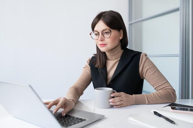 Jeune femme d'affaires contemporaine avec boisson analysant les données financières en ligne devant un ordinateur portable au bureau