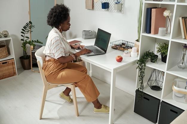 Jeune femme d'affaires contemporaine en réseau par bureau à la maison