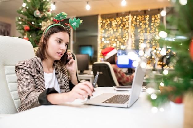 Jeune femme d'affaires contemporaine avec téléphone mobile organisant des travaux pour l'année prochaine devant un ordinateur portable au bureau