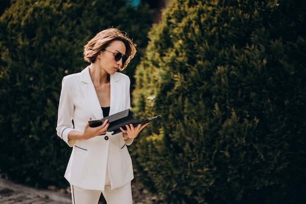 Jeune femme d'affaires en costume blanc, parler au téléphone à l'extérieur
