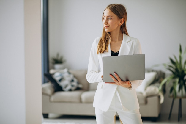 Jeune femme d'affaires en costume blanc travaillant sur un ordinateur