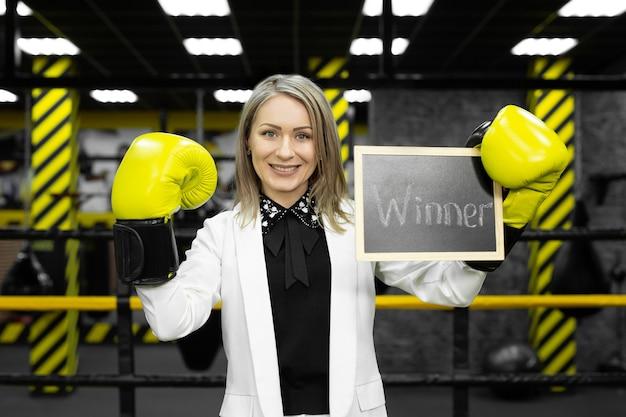 Jeune femme d'affaires en costume dans un ring de boxe avec des gants est titulaire d'un signe avec le gagnant de l'inscription.