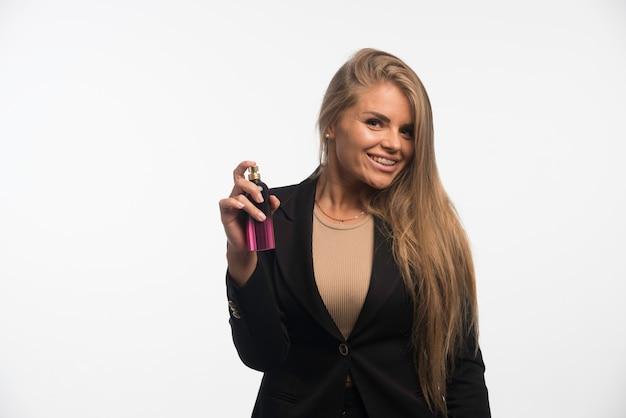 Jeune femme d'affaires en costume noir applique le parfum et les sourires.
