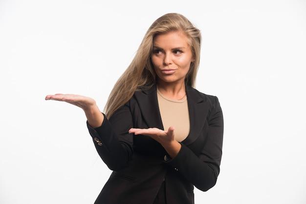 Jeune femme d'affaires en costume noir introduisant quelque chose.