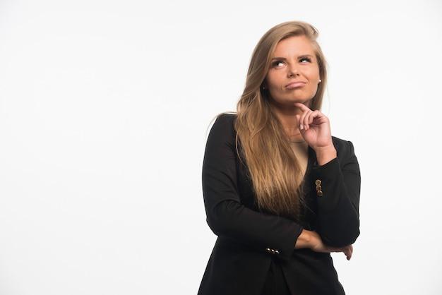 Jeune femme d'affaires en costume noir en levant et en pensant