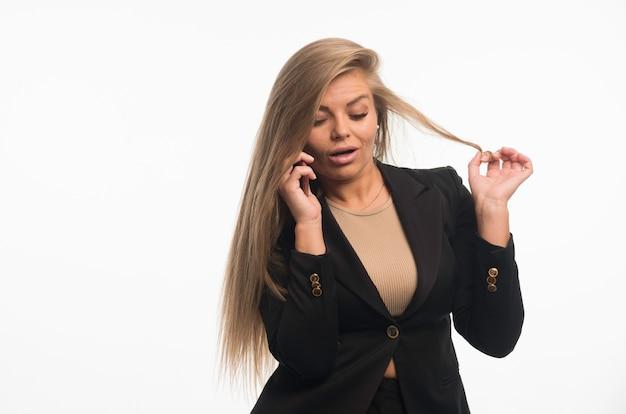 Jeune femme d'affaires en costume noir, parler au téléphone et a l'air sérieux.