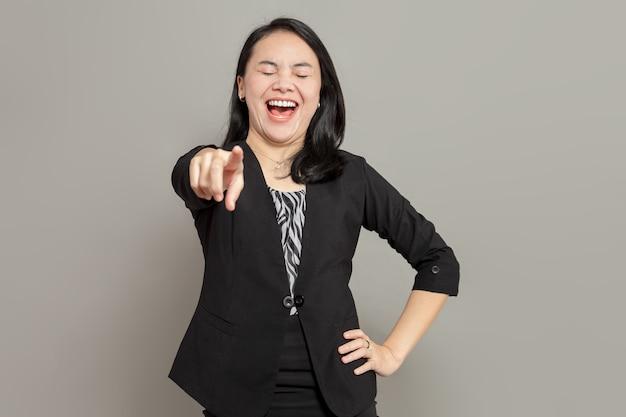 Jeune femme d'affaires en costume noir pointant vers l'avant en riant