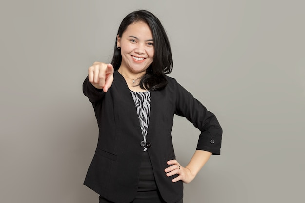 Jeune femme d'affaires en costume noir pointant vers l'avant avec le sourire