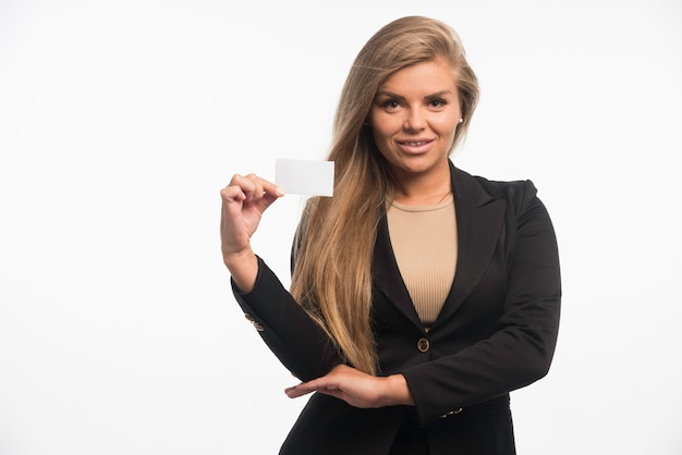 Jeune femme d'affaires en costume noir vérifiant la carte de visite du client et souriant.