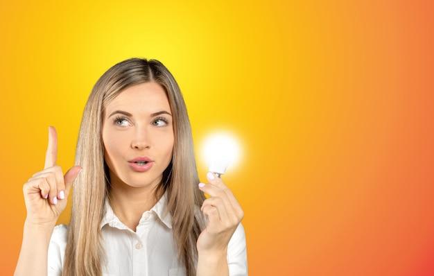Jeune femme d'affaires à côté du symbole de l'ampoule rougeoyante