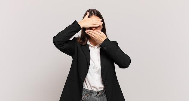 Jeune femme d'affaires couvrant le visage avec les deux mains disant non à la caméra ! refuser des photos ou interdire des photos