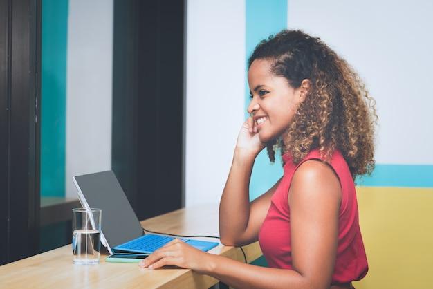 Jeune femme d'affaires créative parler sur smartphone tout en travaillant avec un ordinateur portable au bureau