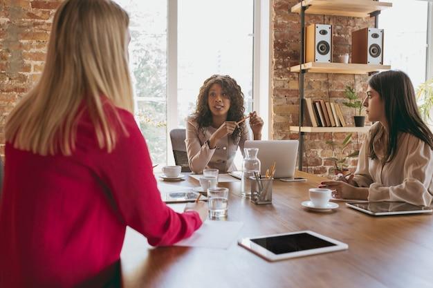 Jeune femme d'affaires dans un bureau moderne avec équipe. réunion créative, attribution de tâches. projet de travail en équipe. concept de finance, d'affaires, de pouvoir des filles, d'inclusion, de diversité, de féminisme. discussion.
