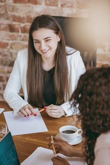 Jeune femme d'affaires dans un bureau moderne avec équipe. réunion créative, discussion, travail de projet. concept de finance, d'affaires, de pouvoir des filles, d'inclusion, de diversité, de féminisme. il a l'air heureux et attentif.