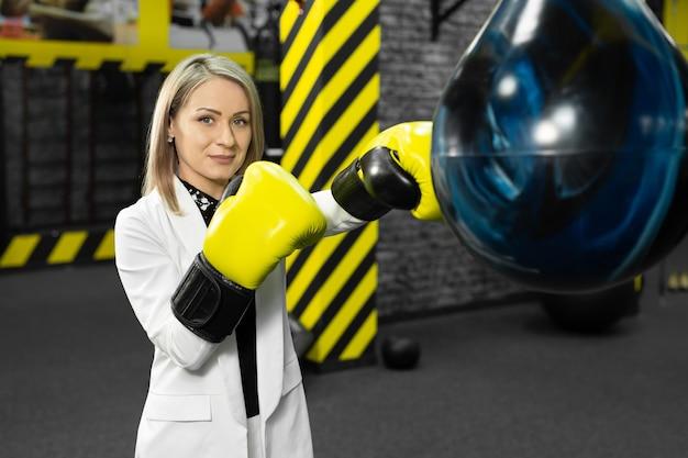 Jeune femme d'affaires dans un costume blanc frappe un sac de boxe dans la salle de gym. le concept de la colère et de la relaxation des employés de bureau.