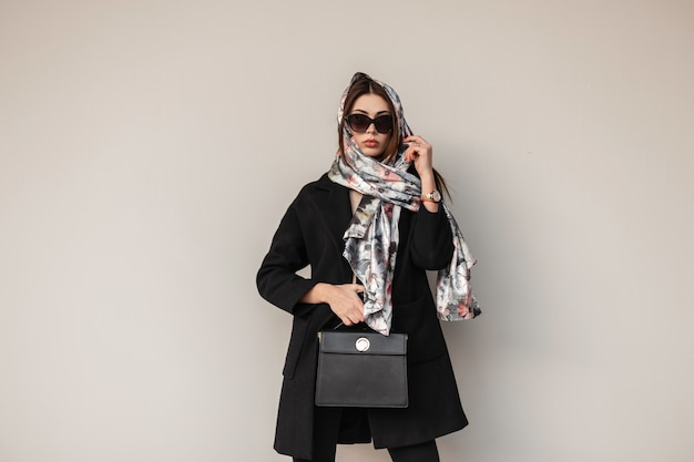 Jeune femme d'affaires dans des lunettes de soleil élégantes dans un manteau noir avec un sac à main en cuir à la mode dans une écharpe glamour posant près d'un mur vintage dans la rue. jolie fille à la mode. dame élégante.