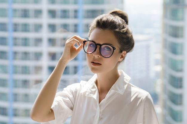 Jeune femme d'affaires dans son bureau dans le bâtiment moderne de la grande ville