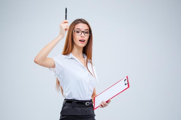 La jeune femme d'affaires dans des verres avec un stylo et une tablette pour des notes sur un espace gris