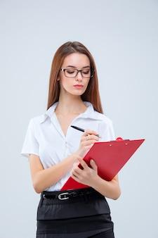 La jeune femme d'affaires dans des verres avec un stylo et une tablette pour des notes sur un gris
