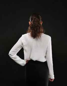 Jeune femme d'affaires debout en arrière sur fond noir