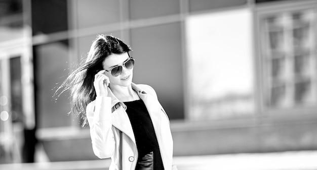 Jeune femme d'affaires debout dans la rue près de l'immeuble de bureaux