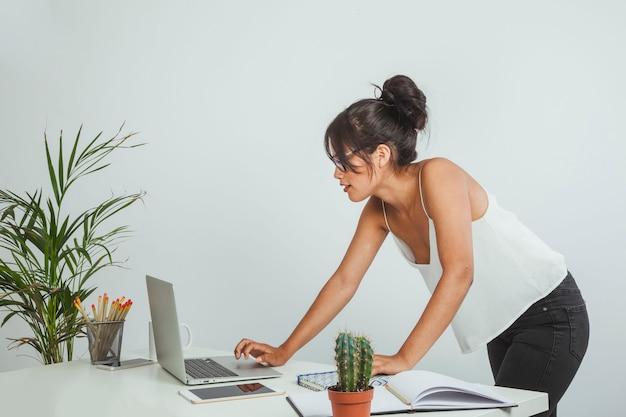Jeune femme d'affaires debout et travaille avec un ordinateur portable