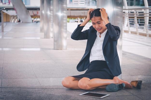 Jeune femme d'affaires déprimée assis sur le sol