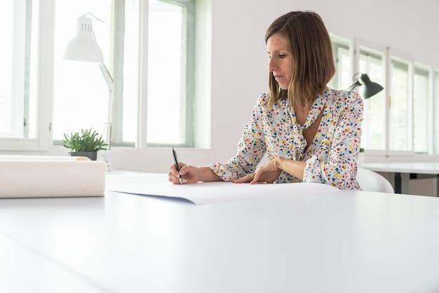 Jeune femme d'affaires ou designer assise à son bureau travaillant sur un projet de dessin au crayon sur une grande feuille de papier.
