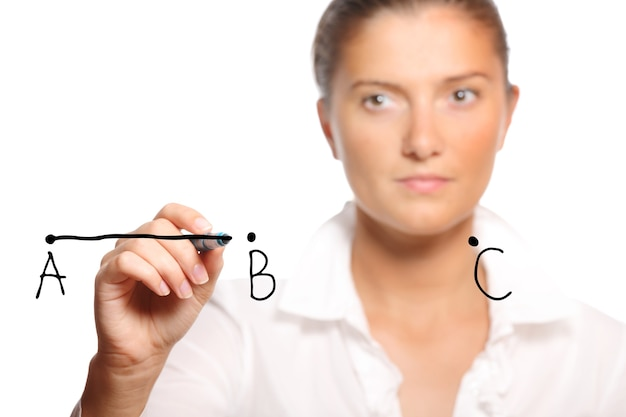 Jeune femme d'affaires dessinant une ligne sur fond blanc
