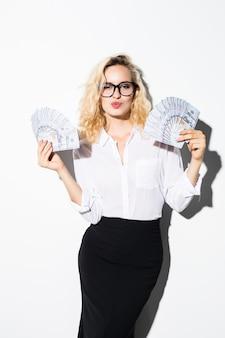 Jeune femme d'affaires détenant de l'argent avec sourire isolé sur un mur blanc.