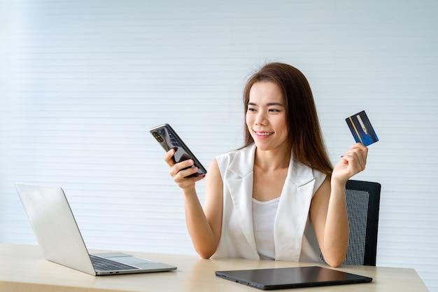 Jeune femme d'affaires détenant une carte de crédit et à l'aide de smartphone