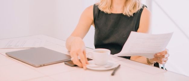 Jeune, femme affaires, document, papier, main, tenue, tasse café, lieu de travail