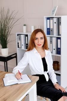 Jeune femme d'affaires écrit dans un cahier au bureau