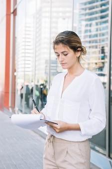 Jeune femme d'affaires écrit sur le presse-papiers avec stylo