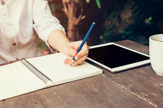 Jeune femme d'affaires avec écriture au crayon sur le cahier. femme à la main avec une écriture au crayon sur un cahier et travailler au café.
