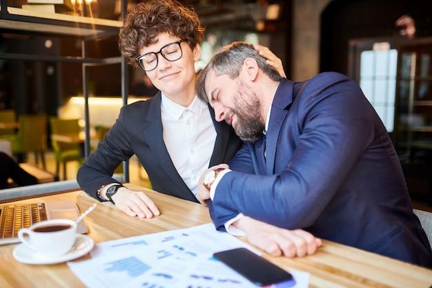 Jeune femme d'affaires élégante consolant son collègue frustré lors de l'analyse des documents financiers