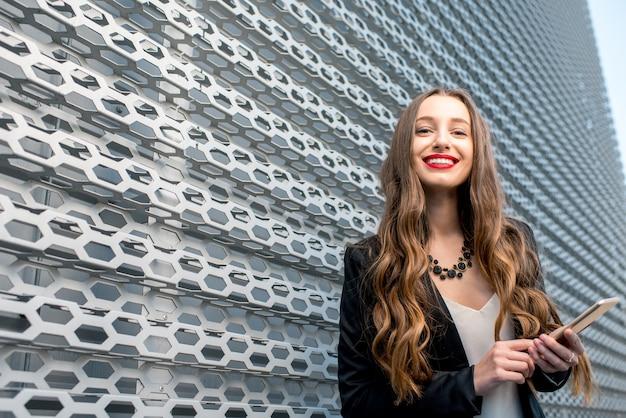 Jeune femme d'affaires élégante en costume debout à l'extérieur avec un téléphone près du mur métallique moderne