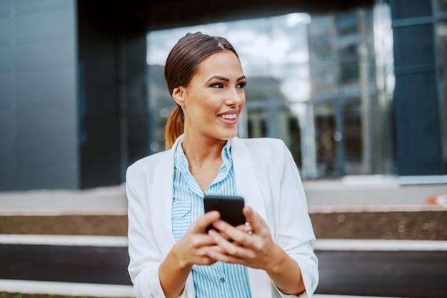 Jeune femme d'affaires élégante souriante attrayante debout devant l'entreprise, tenant un téléphone intelligent et en détournant les yeux.