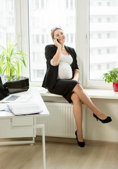 Jeune femme d'affaires enceinte parlant au téléphone au bureau