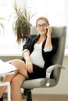 Jeune femme d'affaires enceinte sur son lieu de travail au bureau